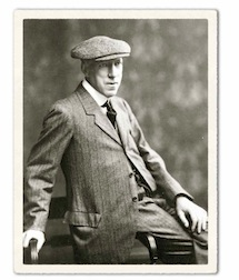 Cecil Sharp, a man with rather a long face, perched on the arm of a wooden chair formally dressed in a tweed suit and wearing a large flat cap