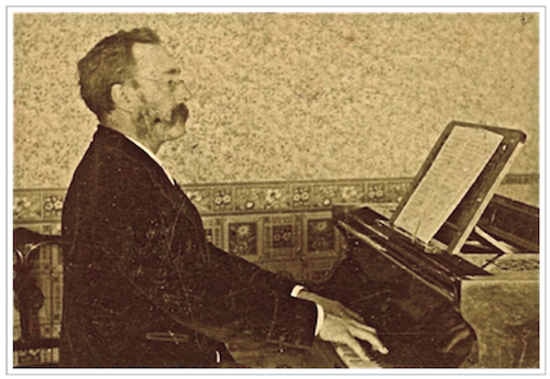 Side view of James Shaw in velvet smoking jacket and handlebar moustache playing on a grand piano in his music roomdrawing room