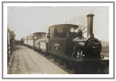 A narrow gauge railway train  arrives at Southwold station