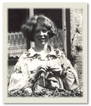 a young woman with thick curly hair cut into a bob, wearing an embroidered smock, looks over from a low hedge knitting.  Behind her is a cottage window with broderie anglaise type net curtain